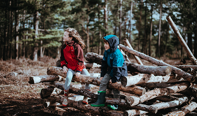 Nens jugant sobre troncs