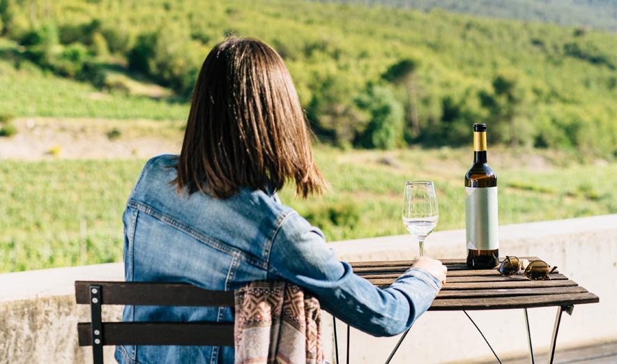 dona asseguda amb una copa de vi