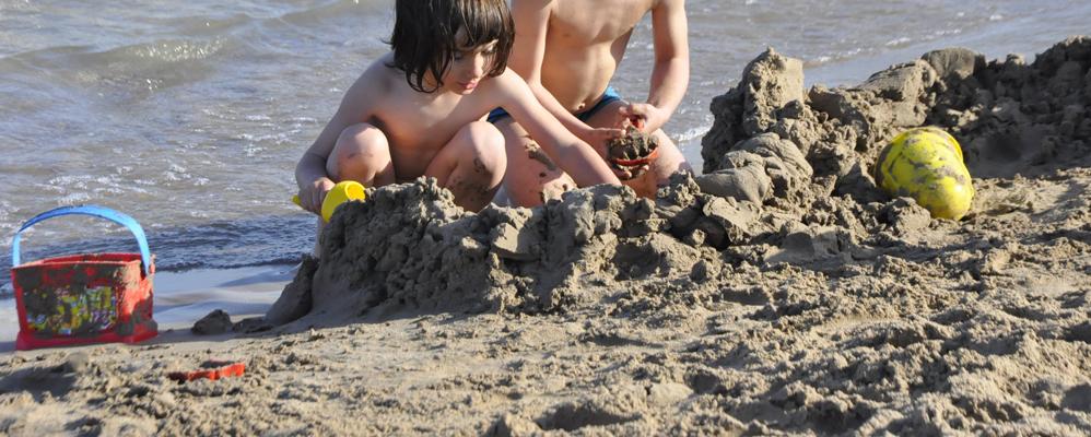 Uns nens juguen a la platja del far de Vilanova